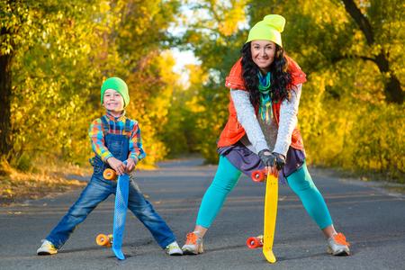 Sourire, femme et garçon, debout largeur plastique de couleur carte de penny extérieure planche à roulettes.