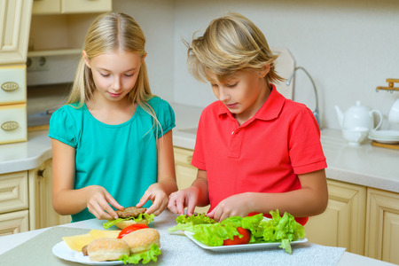 sourire garçon heureux et fille faisant des hamburgers ou des sandwichs maison.