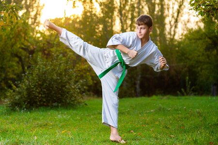 boys in white kimono during training karate exercises at summer outdoors. Banque d'images