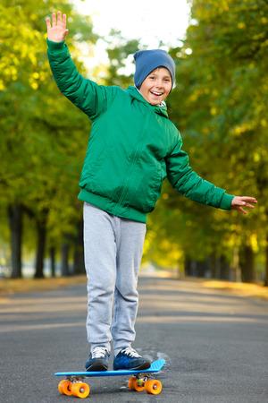 Sourire garçon debout sur la couleur en plastique carte de penny ou planches à roulettes en plein air. Banque d'images