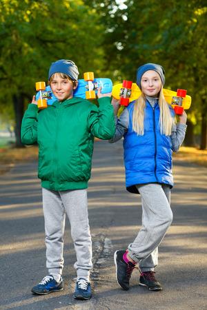 Sourire garçon et fille tenant couleur plastique conseils penny ou planches à roulettes extérieure.