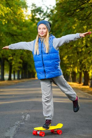 Sourire fille posant sur la couleur en plastique carte de penny ou planches à roulettes en plein air. Banque d'images