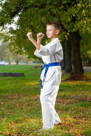 kleine jongen in witte kimono tijdens de training karate oefeningen in de zomer buiten. Stockfoto