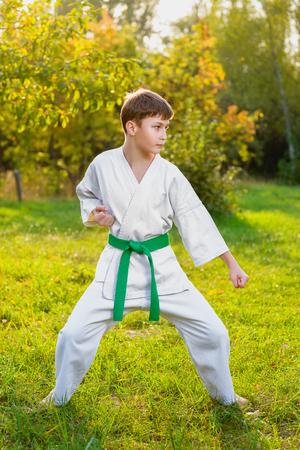 jongens in witte kimono tijdens de training karate oefeningen in de zomer buiten.