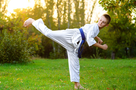 little boy in white kimono during training karate exercises at summer outdoors.