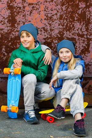 Lachende jongen en meisje met kleur plastic penny boards of skateboards outdoor. Stockfoto