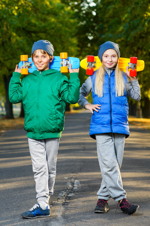 Glimlachend jongen en meisje bedrijf kleur plastic cent boards of skateboards outdoor.