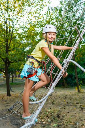 Gelukkig kind te genieten van actieve zomervakantie. Schattig klein kind, blond schattige peuter meisje, met plezier buiten klimmen op speelplaats in het park op zonnige dag.