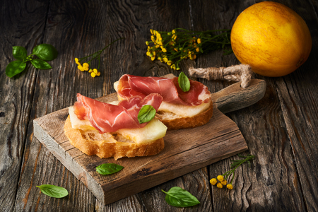 photo of tasty bread slices with bacon and melon Stockfoto