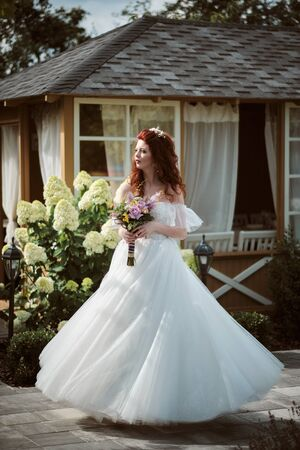 Young bride wearing wedding dress and posing outside
