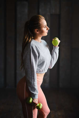 athletic young woman doing a sport fitness workout with dumbbells at gym