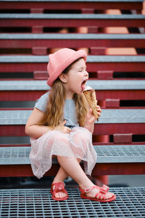 funny and happy little girl in hat eating ice cream