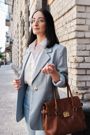stylish businesswoman standing with bag on the city street