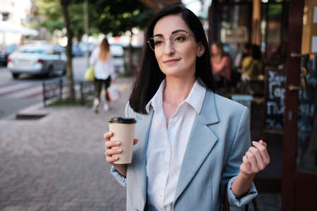 smiling businesswoman holding cofee in urban background Stockfoto