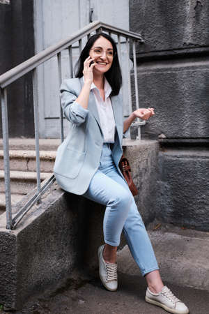 Happy smiling businesswoman with cellphone in a urban background Stockfoto