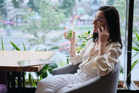 smiling businesswoman talking cellphone in city cafe