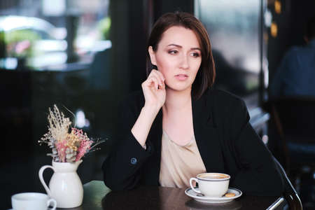 pensive or thoughtful woman sitting at table in cafe wearing black jacket