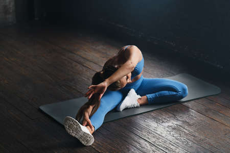 Sports concept. Young woman doing stretching exercises at gym