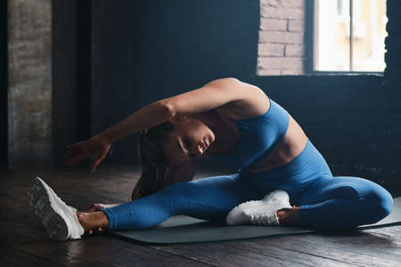 Sports concept. Young woman doing stretching exercises at gym Stockfoto - 152799206