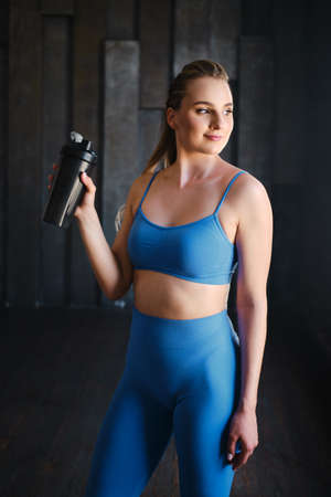 beautiful woman going to drink some water from plastic bottle after workout