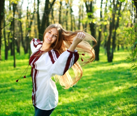 Smiling cute girl with long hair dancing in green park photo