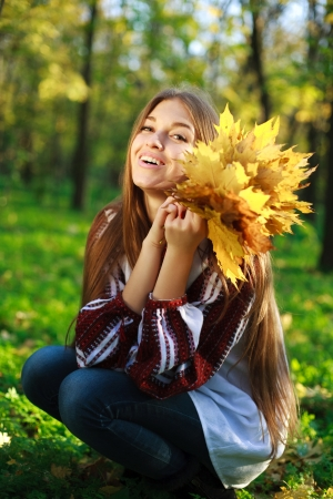 16 year old girls: Pretty laughing girl with yellow leafs in his hands, in green park Stock Photo