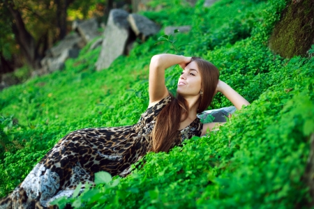 Smiling young girl lying on green grass close up,in park  photo