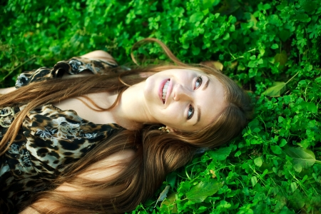 16 year old girls: Happy young girl lying on green grass close up,enjoy rest in summer park