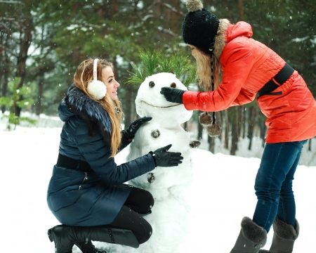 Two happy pretty girls building a snowman in pinewood on a winter day photo