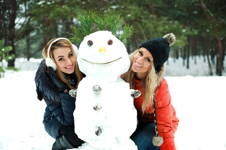 Two happy pretty girls with snowman in pinewood on a winter day Stock Photo - 17415400