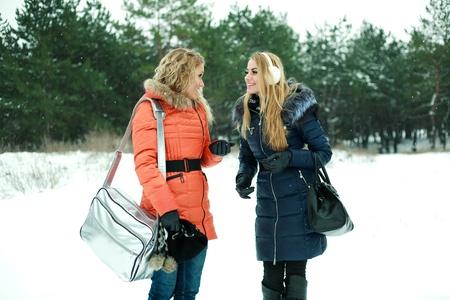 Two happy pretty girls walking in pinewood on a winter\ day