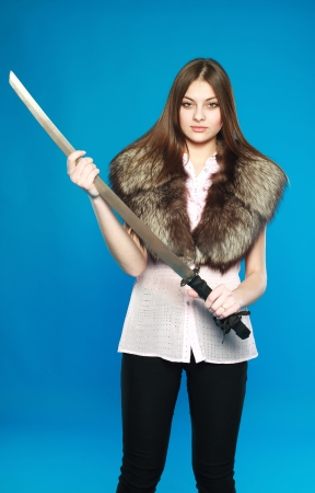 Young brunette standing with a sword in hand, in the studio on a blue background Stock Photo - 17565504