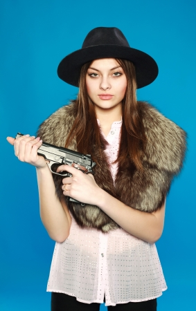 A young girl in a black hat with a gun in his hand, in the studio on a blue background photo