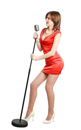 Attractive young girl in a red dress singing into a microphone, studio, isolated on white Stok Fotoğraf