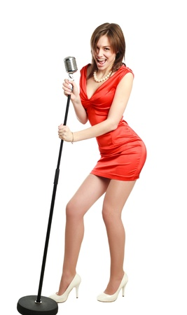 Attractive young girl in a red dress singing into a microphone, studio, isolated on white photo