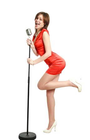 Attractive young girl in a red dress singing into a microphone, studio, isolated on white 版權商用圖片