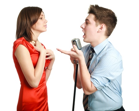Young guy singing to a pretty girl, studio, isolated on white background
