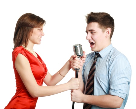 Young guy singing to a pretty girl, studio, isolated on white background photo
