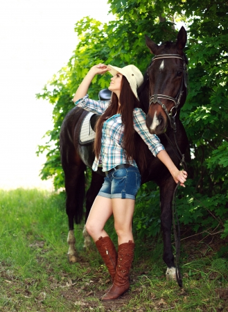 western saddle: Outdoor portrait of beautiful cowgirl  with horse in the green forest