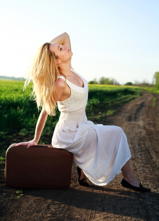 Beautiful blonde girl in long white dress, sitting on suitcase at countryside, on lonely road  photo