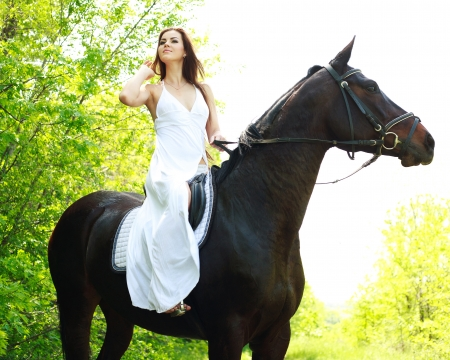 Young beautiful girl riding on horse in the green forest Stock Photo