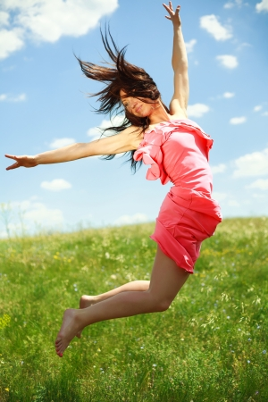 Jumping and flying graceful girl on the background of blue sky and clouds photo