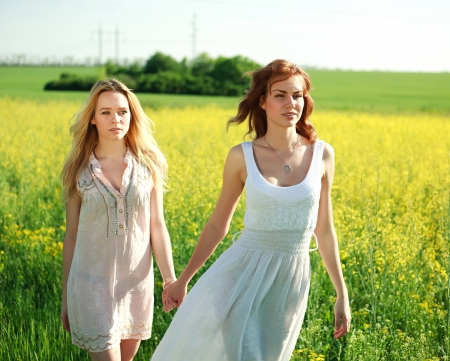 Two girlfriends in long dresses, together outdoors, portrait in the summer field Stock Photo - 21472053