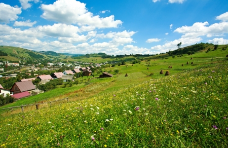 Summer landscape in the Carpathian villages under a blue sky with white clouds photo