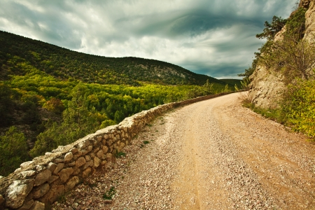 The old rocky road in the Crimean mountains, under mysterious cloudy sky photo