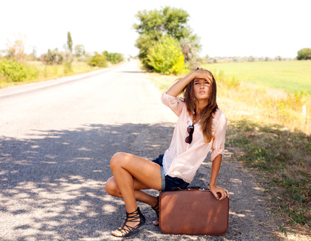 hitch hiker: Staring into the distance woman, sitting on a suitcase by a countryside road Stock Photo