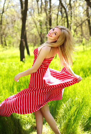 Adorable summer young woman in long red dress, carefree dancing enjoying nature