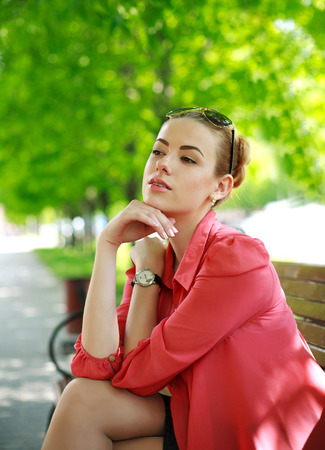 Young woman sitting on bench in green park, thoughtfully looking away