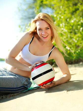 Young sporty woman with ball on the beach, green background photo
