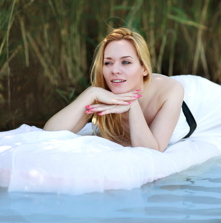 Young woman lies on a white water bed, relaxing outdoors on background of green plants photo